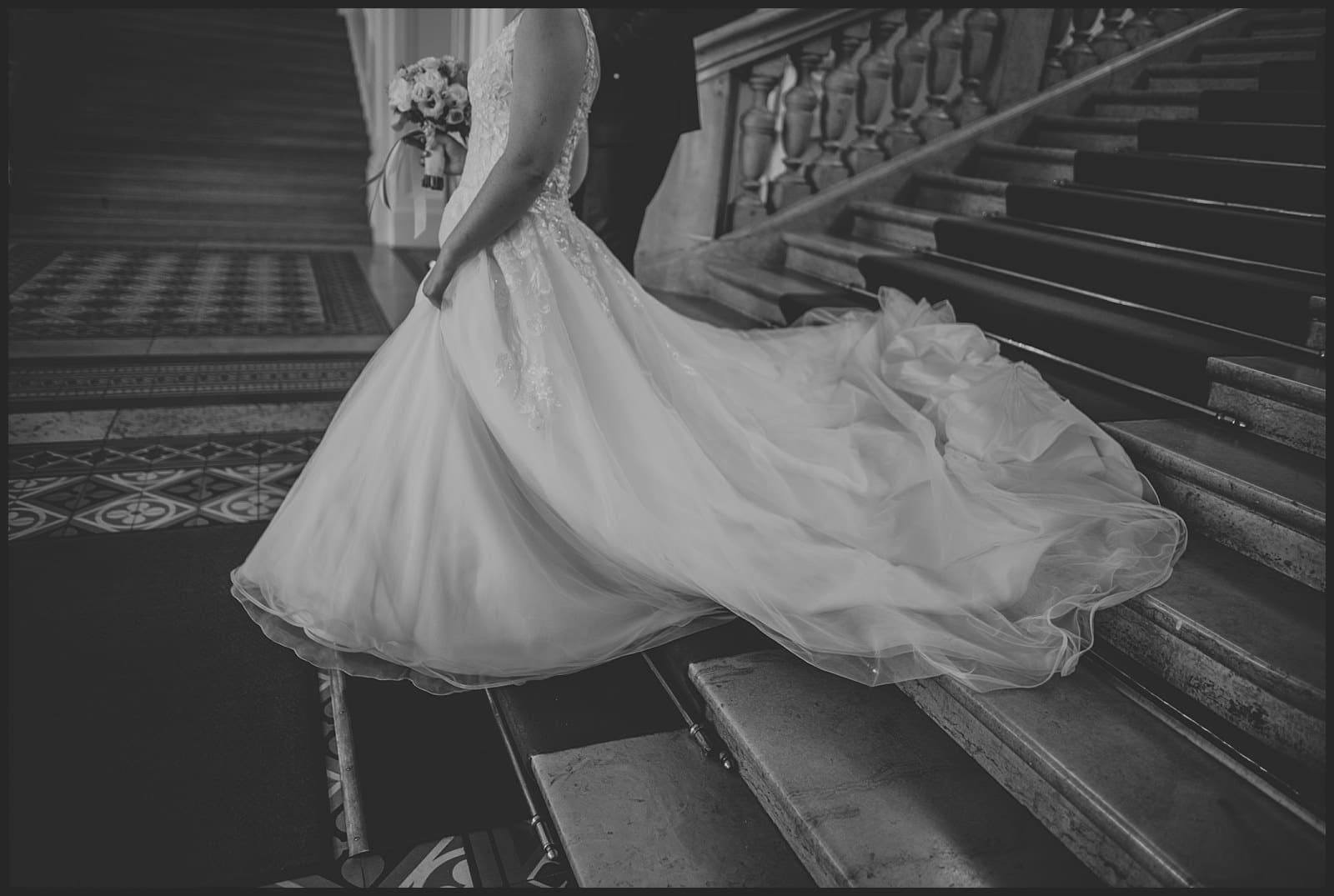 détail robe de la mariée pendant qu'elle descend les marches à la mairie de Limoges
